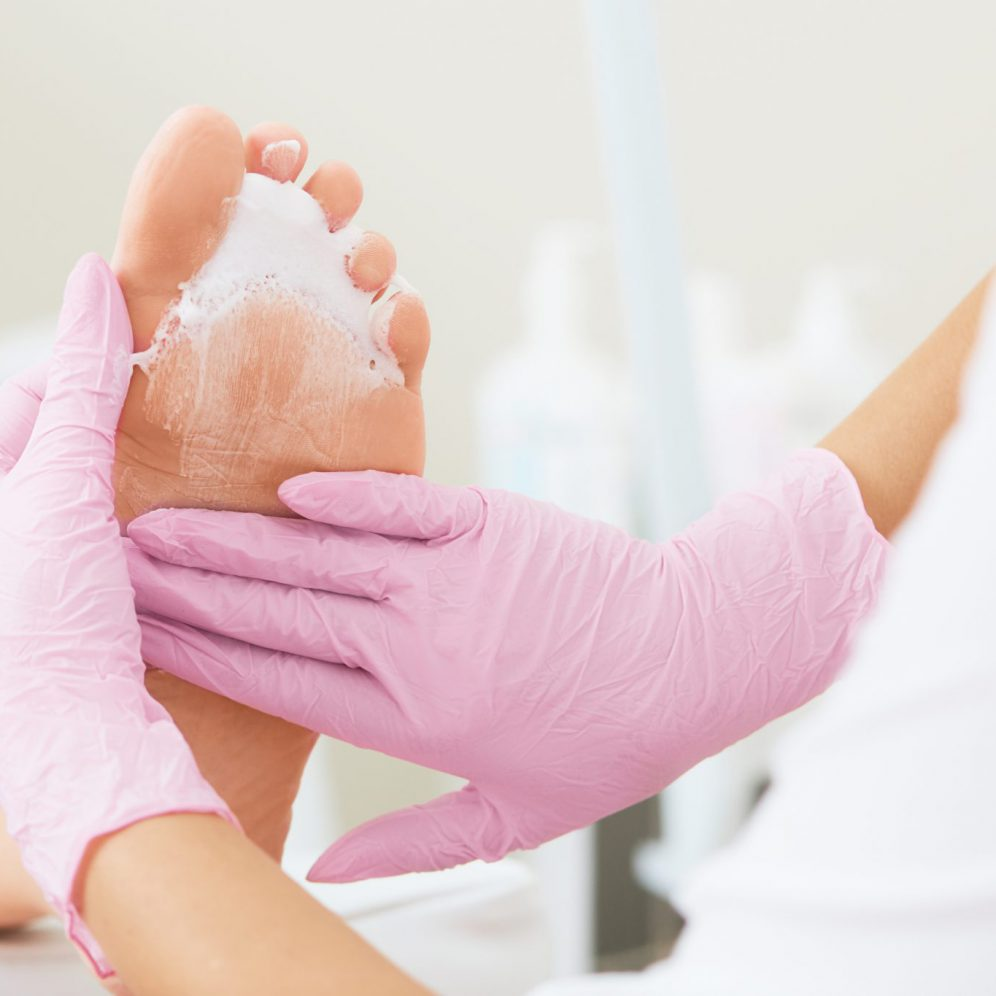 Professional foot massage using moisturizing foam.Final stage of professional pedicure.Skin softener, smoothing out hard skin.Patient visiting podiatrist. Foot treatment in SPA salon.Podiatry clinic.